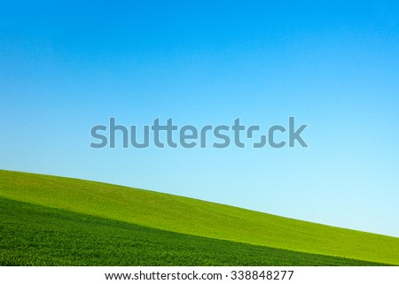 The sloping layered farm fields of a rural landscape on the side of a hill meet a clear blue sky.