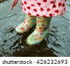 The small child costs in a pool in gumboots, on the child the bright raincoat is put on. Close up children's legs in boots and a big pool. - stock photo