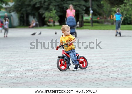 The small white boy toddler  with blond hair and blue jeans is riding on his red children's bike in a city park. Security and protection of children in the performance of tricks on the bike.