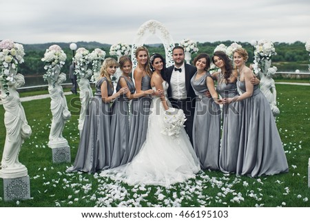 The smilling  bridesmaids with brides stand near statuettes