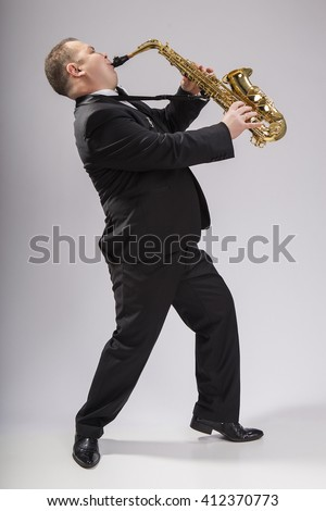 The soloist, saxophonist plays the saxophone. Dressed in a suit. Man.