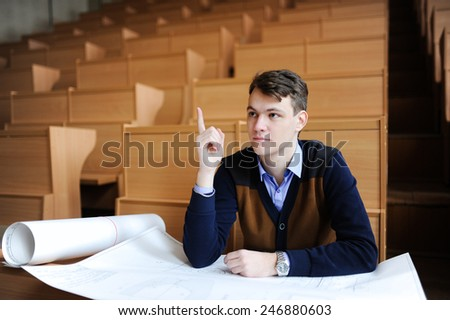 The student in large audience, sitting at a school desk, prepares for examination