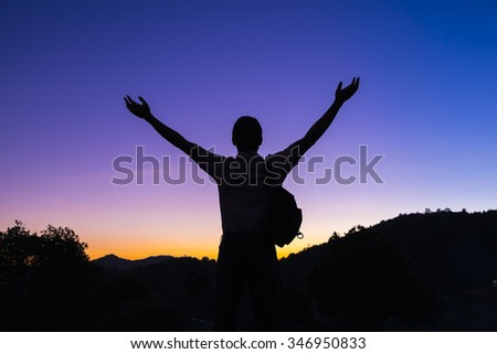 The success concept of silhouette of young man standing made arms rising, Under rising sun.