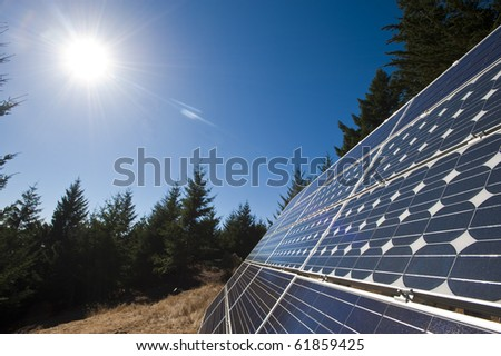 The sun beams down on multiple solar panels along the northern California coast.