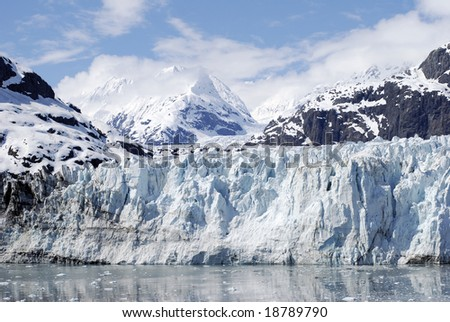 The view of the blue glacier with mountains in a background in Glacier Bay national park, Alaska.