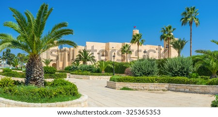 The view on the medieval Ribat fortress behind the green palms of the central park, Monastir, Tunisia.