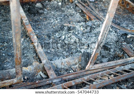 The wagons of the train that were burned in a fire in an accident. The fire destroyed the wagons, and some have been distorted by the excessive heat. There are only embers and ashes.