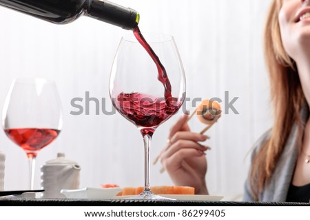 The waiter pours wine into a glass for a woman eating maki with chopsticks on a background