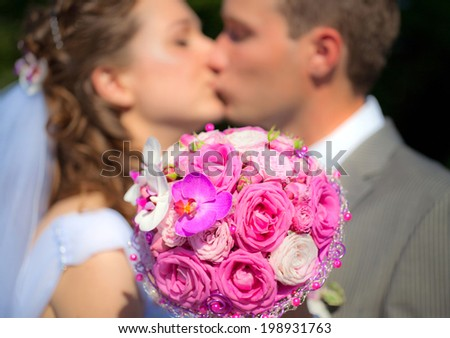 The Wedding Bouquet with Bride and Groom on the Background