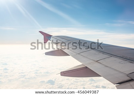 The wing of airplane among cloud ,blue sky and sunlight