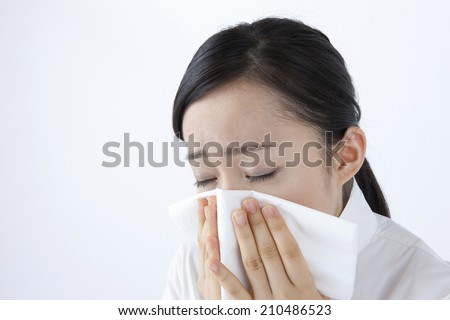 The woman blowing her nose