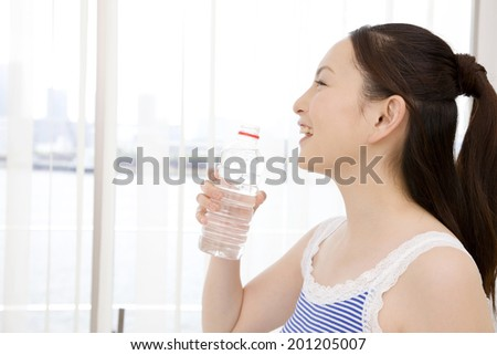 The woman drinking a bottled water