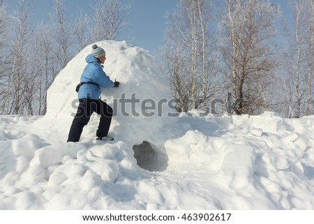 The woman in a blue jacket building an igloo on a snow glade in the winter