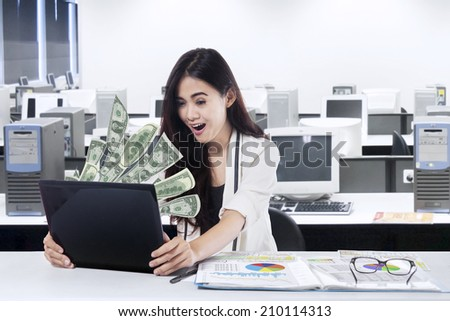 The woman in front of the laptop with fly out dollars
