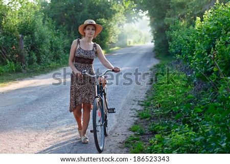 The woman of middle age  in straw hat with bicycle.