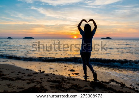 The woman stands on the beach in twilight time./silhouette./Love/Valentines day