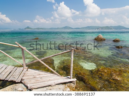 The wooden bridge and stones at the beautiful sea and blue sky.