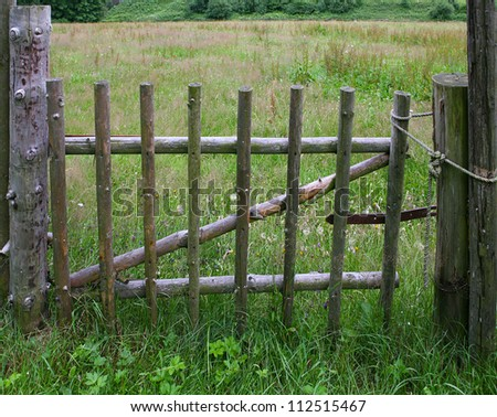 The wooden gate on the meadow