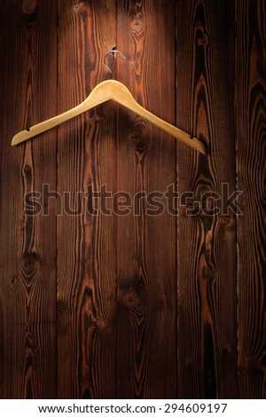 The wooden hanger hangs on a wooden wall