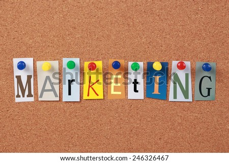 the word marketing in cut out magazine letters pinned to a cork board