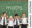 The word maths against cute pupils showing thumbs up in classroom - stock photo