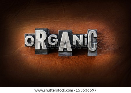 The word organic made from vintage lead letterpress type on a leather background.