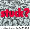 The word Stuck on a background of question marks to illustrate being caught in a sticky situation, problem, trouble or issue and thinking of a way out or answer - stock photo