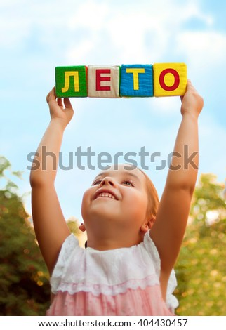 "The word ""Summer"" in Russian in the hands of the child of soft cubes in the sky"