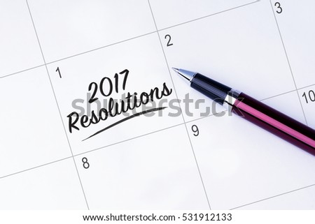 The words 2017 Resolutions written on a calendar planner to remind you an important appointment with a pen on isolated white background. New Year concepts of goal and objective.