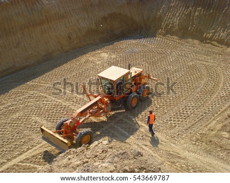 The worker is ready to climb into grader