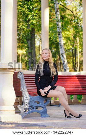 The young beautiful woman on a bench in the park
