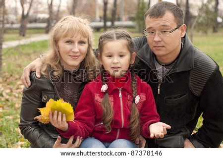 The young family in park, sits on a grass and smiles