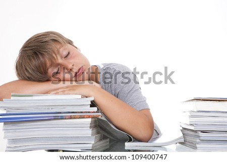 The young student sleeps on the books. Studio shot.