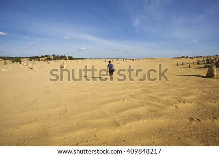 The young traveler in black t-shirt is walking through desert with his camera. Desert landscape