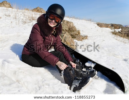 The young woman puts legs in boots for a snowboard, she sit on snow
