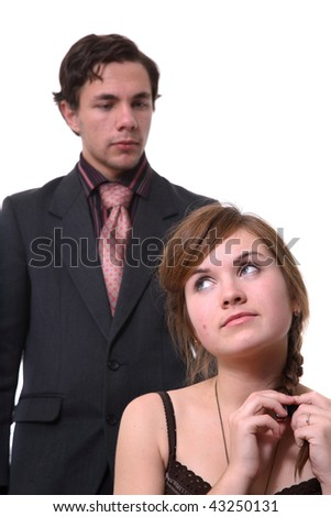 The young woman tensely touches hair, behind there is a young man