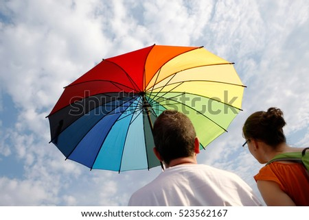 THESSALONIKI, MAKEDONIA/GREECE   JUNE 6: Boy and Girl under a Rainbow Umbrella looking at the sky on June 6 2015 in Thessaloniki. They were participating in the Gay Parade of that day.