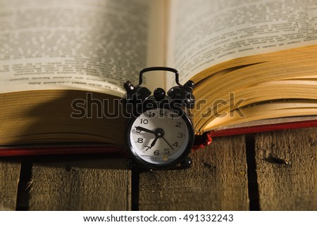 Thick Book Lying Open On Wooden Surface, Old Fashioned Night Table Clock  Sitting Next To