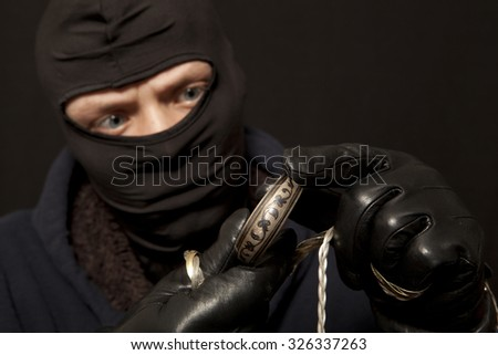 Thief. Man in black mask with a silver bracelet. Focus on bracelet