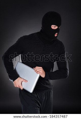 Thief stealing a laptop computer creeping furtively through the darkness as he makes his getaway  conceptual of data and identity theft