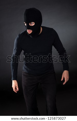 Thief wearing a balaclava dressed in blacked moving stealthily through the darkness as he prepares to commit robbery