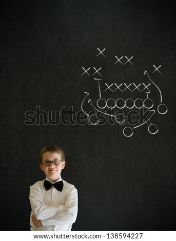Thinking boy dressed up as business man with chalk American football strategy on blackboard background