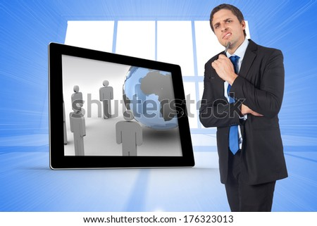 Thinking businessman holding pen against bright blue room with windows