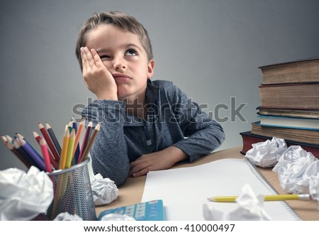 Thinking child bored, frustrated and fed up doing his homework