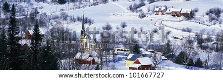 This is an aerial view of a town in Vermont. There is a black steepled church and a small village. The village is covered in snow with houses spread across the field.