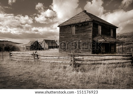 This quiet ghost town ranch in the Dallas Divide near Ouray and Telluride Colorado glows under soft daylight with a light sepia tone added to the black and white image to emphasize the aged look.