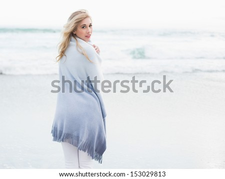 Thoughtful blonde woman warming herself in a blanket on the beach