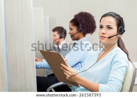 Thoughtful female customer service agent holding clipboard with colleagues working in background at call center