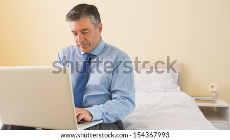 Thoughtful mature man using a laptop sitting on a bed in a bedroom