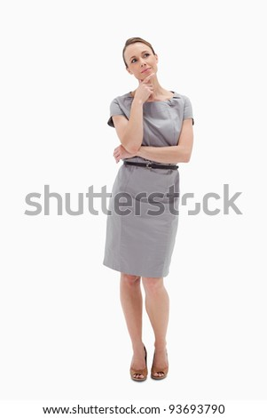 Thoughtful woman posing in dress against white background